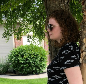 Picture of Ashley outside resting against a tree trunk