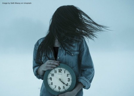 woman holding clock with hair blowing and gray behind her