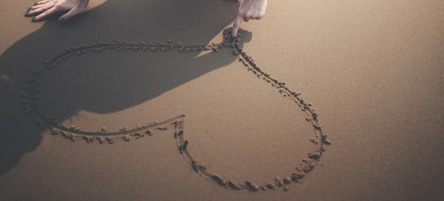 Picture of a heart drawn in the sand.