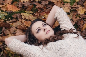 woman lying on leaf-covered ground